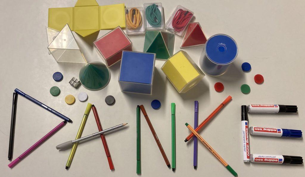 Das Wort Danke wird auf einem Tisch durch Stifte und andere Unterrichtsmittel dargestellt.